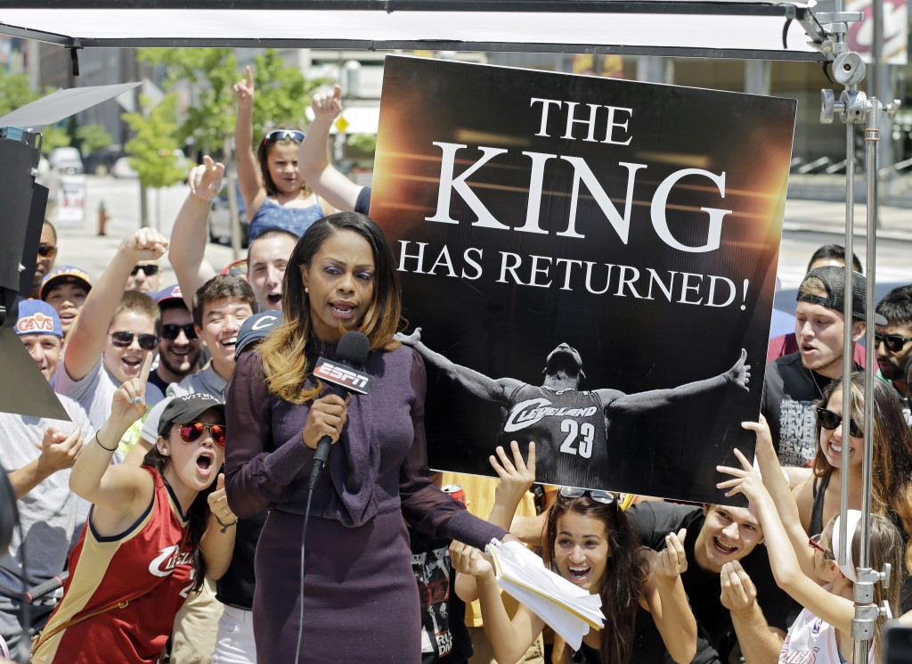 Fans whoop it up behind an ESPN reporter outside Quicken Loans Arena in Cleveland, after NBA basketball star LeBron James announced he would return to the Cleveland Cavaliers Friday, July 11, 2014. (AP Photo/Mark Duncan)