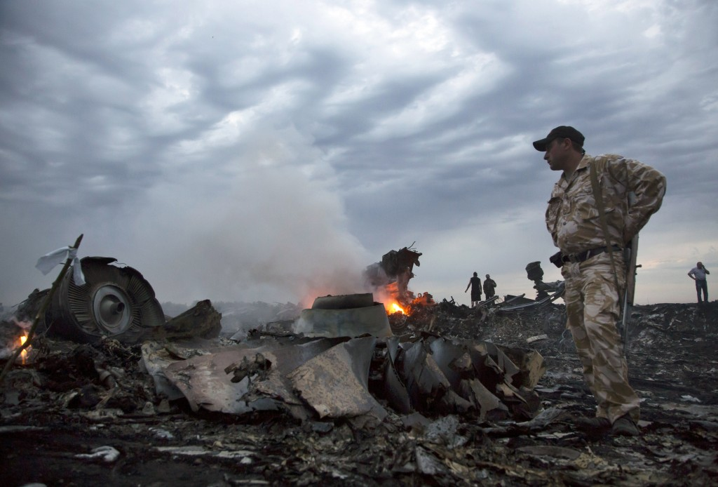 People walk amongst the debris, at the crash site of a passenger plane near the village of Grabovo, Ukraine, Thursday, July 17, 2014.  A Ukrainian official said a passenger plane carrying 295 people was shot down Thursday as it flew over the country and plumes of black smoke rose up near a rebel-held village in eastern Ukraine. Malaysia Airlines tweeted that it lost contact with one of its flights as it was traveling from Amsterdam to Kuala Lumpur over Ukrainian airspace.  (AP/Dmitry Lovetsky)