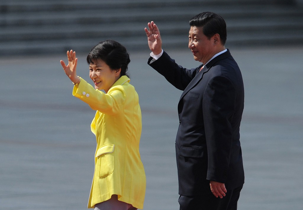 South Korean President Park Geun-hye, left, and Chinese President Xi Jinping wave during a welcoming ceremony outside the Great Hall of the People in Beijing Thursday, June 27, 2013. The Chinese and South Korean presidents reaffirmed close ties between their nations Thursday at a Beijing summit that brings together North Korea's archrival and its biggest ally, ratcheting up pressure on Pyongyang to rejoin nuclear disarmament talks. (AP Photo/Wang Zhao, Pool)