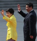 South Korean President Park Geun-hye, left, and Chinese President Xi Jinping wave during a welcoming ceremony outside the Great Hall of the People in Beijing Thursday, June 27, 2013.  (AP Photo/Wang Zhao, Pool)
