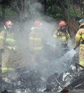 Firefighters work at the site of a helicopter crash that killed all five firefighters onboard in a residential area of Gwangju, Thursday. (Yonhap)