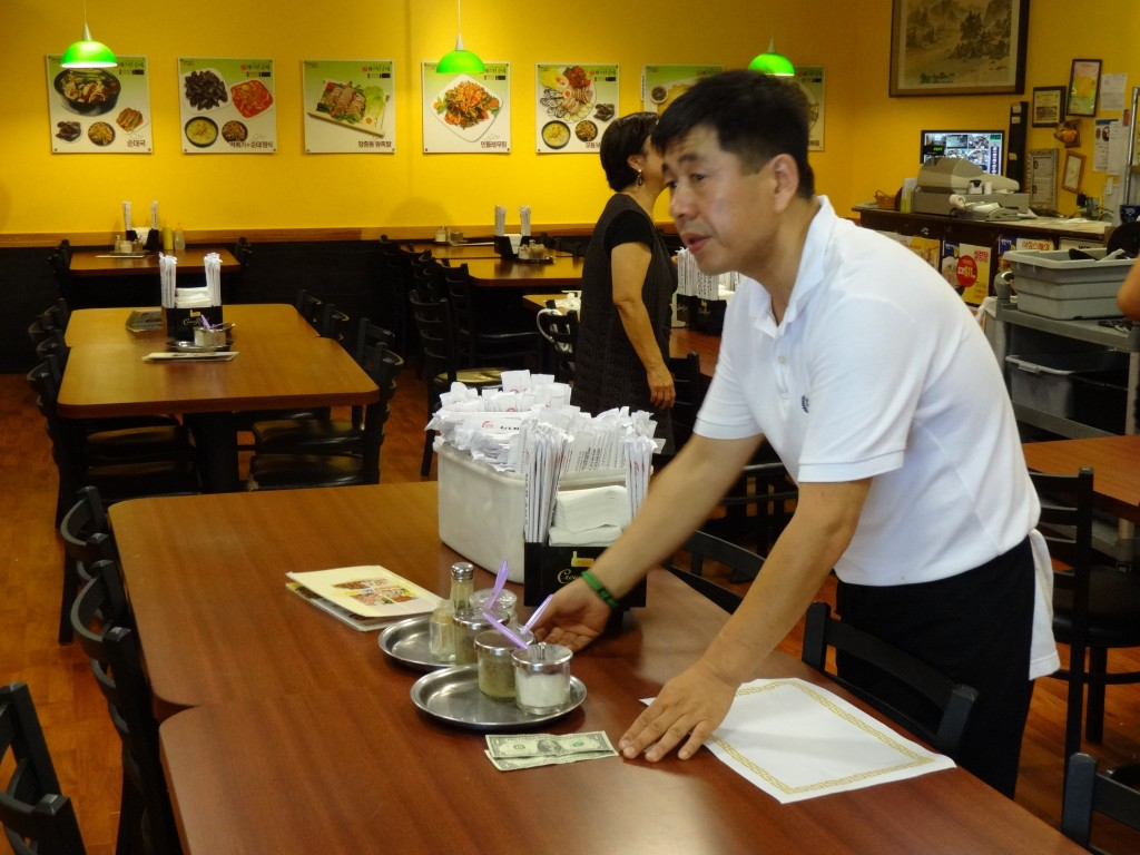 A waiter picks up a tip left at a table in a Koreatown restaurant.