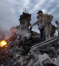 People inspect the crash site of a passenger plane near the village of Grabovo, Ukraine, Thursday, July 17, 2014.  Koreans experienced similar attack some three decades ago, when Soviet forces shot down Korean Air Lines Flight 007.  (AP Photo/Dmitry Lovetsky)