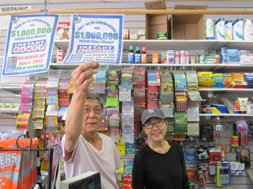 Korean market owners Hwang Sung-hyo and Hwang Hye-sook show off the certificate for the latest $1 million ticket to emerge from their store.