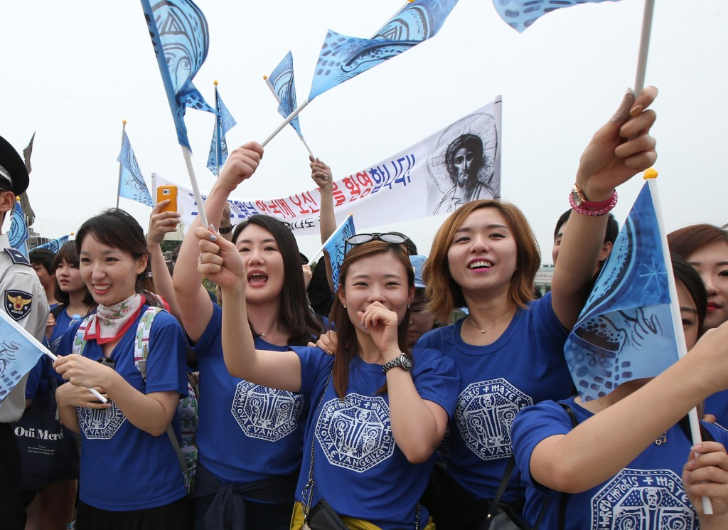 Catholic youths cheer as Pope Francis' car drives by the presidential Blue House Thursday. (Yonhap)
