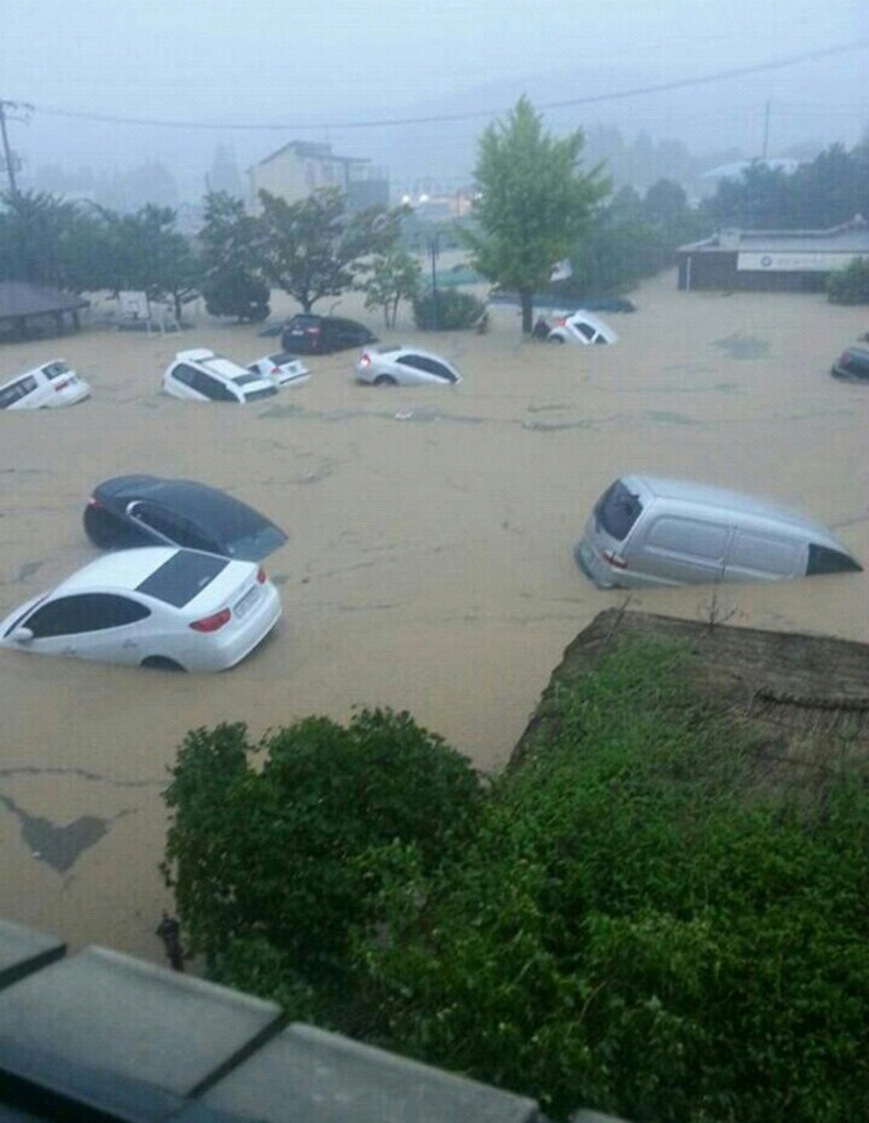 Cars are afloat in a flooded area in Geumjeong, Busan, Monday. Heavy rain hit the southern part of the country, causing flash floods, landslides, and suspension of subway service in some areas. (Yonhap)