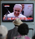 People watch a live TV news program showing Pope Francis' arrival at the Seoul Railway Station in Seoul, South Korea, Thursday, Aug. 14, 2014. Pope Francis arrived Thursday in South Korea on the first papal visit to the Asian nation in a quarter century, stepping off the plane onto a red carpet and greeting President Park Geun-hye. (AP Photo/Lee Jin-man)