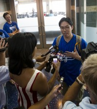 Sung Woo Lee, center, speaks to the local media after arriving at Kansas City International Airport Tuesday, Aug. 5, 2014. Lee is a Kanas City Royals fan from South Korea and came to Kansas City to see his first Royals game. He will see five games and throw out the first pitch on Monday (AP Photo/The Kansas City Star, Brian Davidson)