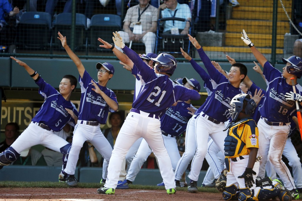 South Korea's Hae Chan Choi (21) celebrates with teammates after hitting a two-run home run off Chicago's Brandon Green in the sixth inning of the Little League World Series championship baseball game in South Williamsport, Pa., Sunday, Aug. 24, 2014. (AP Photo/Gene J. Puskar)