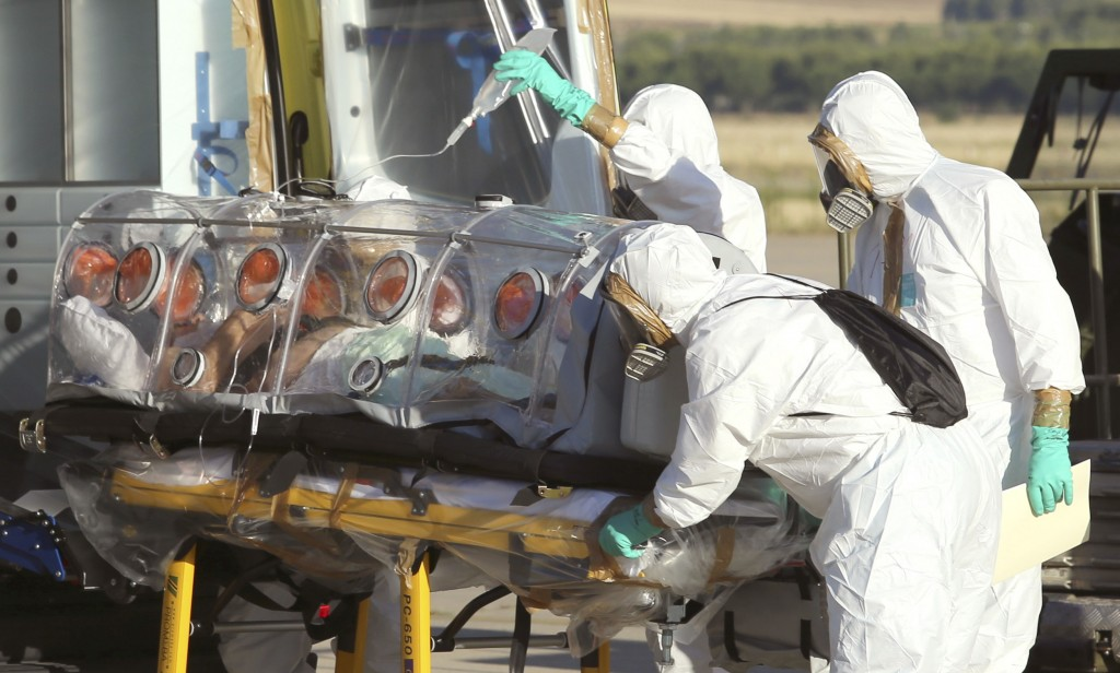 In this photo provided by the Spanish Defense Ministry, aid workers and doctors transfer Miguel Pajares, a Spanish priest who was infected with the Ebola virus while working in Liberia, from a plane to an ambulance as he leaves the Torrejon de Ardoz military airbase, near Madrid, Spain, Thursday, Aug. 7, 2014. Pajares was in stable condition at a Madrid hospital on Thursday after being evacuated from Liberia, health officials said. (AP Photo/Spanish Defense Ministry)