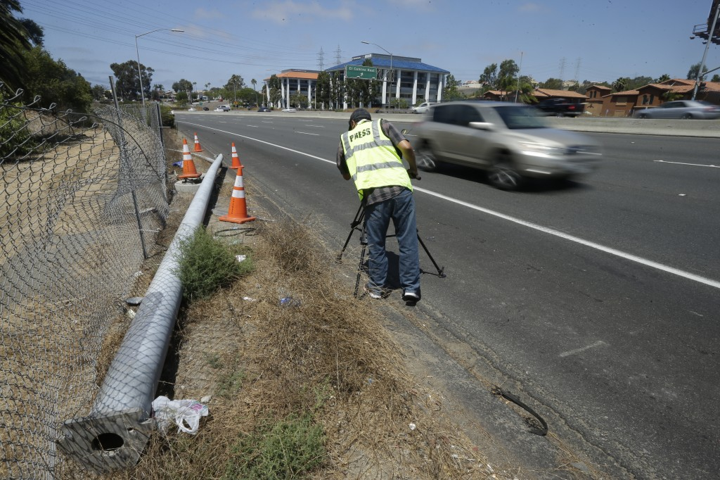 A cameraman films a broken power pole along the highway after a fatal crash Friday, Aug. 22, 2014, in Oceanside, Calif. Three Japanese college students were killed and five other foreign students were injured when a car carrying them veered off a California freeway and struck a power pole, officials said Friday. (AP Photo/Gregory Bull)
