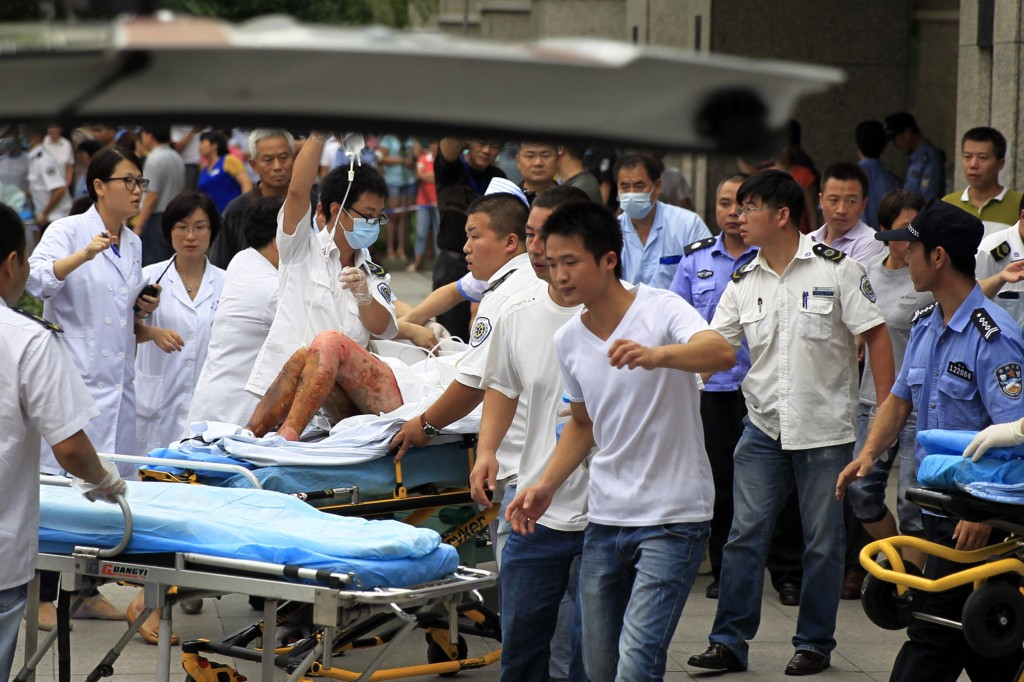 Medical staff move a severely burnt victim of an explosion at an eastern Chinese automotive parts factory from a hospital in the city of Kunshan, Jiangsu province, Saturday, Aug. 2, 2014 to a Shanghai hospital which is better equipped to handle severe burns. Dozens of people were killed Saturday by the explosion at the factory that supplies General Motors, state media reported. (AP Photo)