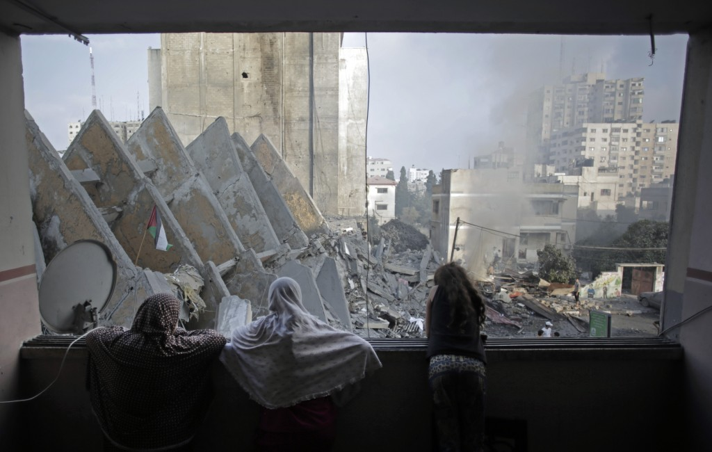 A Palestinian family looks from a window to the rubble of the collapsed 15-story Basha Tower following early morning Israeli airstrikes in Gaza City, Tuesday, Aug. 26, 2014. Israel bombed two Gaza City high-rises with dozens of homes and shops Tuesday, collapsing the 15-story Basha Tower and severely damaging the Italian Complex in a further escalation in seven weeks of cross-border fighting with Hamas. (AP Photo/Khalil Hamra)