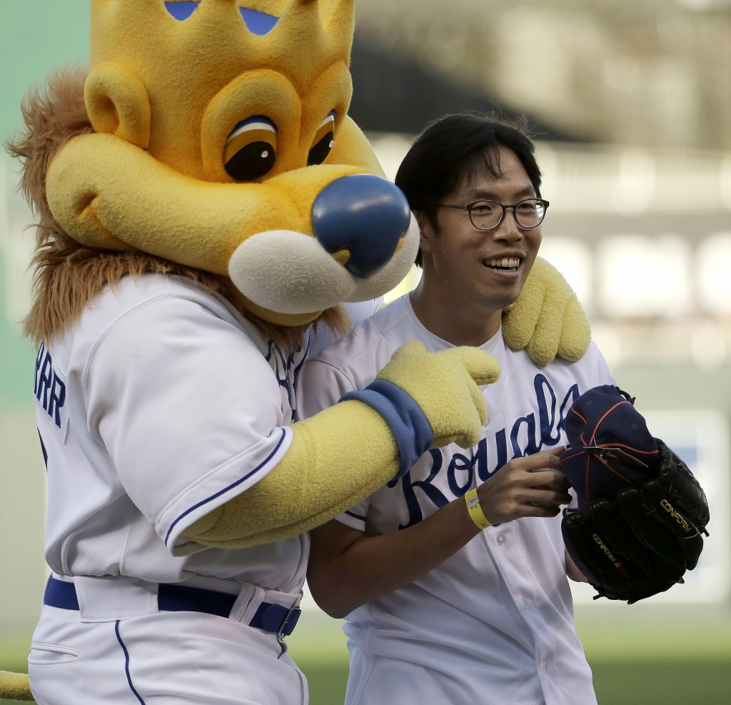 Longtime Kansas City Royals fan Sung Woo Lee, from South Korea, celebrates with Royals mascot Sluggerrr after throwing out the ceremonial first pitch before a baseball game against the Oakland Athletics, Monday, Aug. 11, 2014, in Kansas City, Mo. (AP Photo/Charlie Riedel)