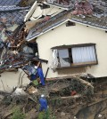 In this aerial photo, rescue workers search for survivors in an area devastated by a massive landslide which swept through residential areas in Hiroshima, western Japan, Wednesday, Aug. 20, 2014. A several people died and at least a dozen were missing after rain-sodden hills in the outskirts of Hiroshima gave way early Wednesday in several landslides. (AP Photo/Kyodo News)