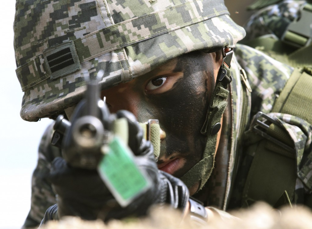 A South Korean marine aims his machine gun during the U.S.-South Korea joint landing exercises called Ssangyong as part of the Foal Eagle military exercises in Pohang, South Korea, Monday, March 31, 2014.  South Korea says North Korea has announced plans to conduct live-fire drills near the rivals' disputed western sea boundary.(AP Photo/Ahn Young-joon)
