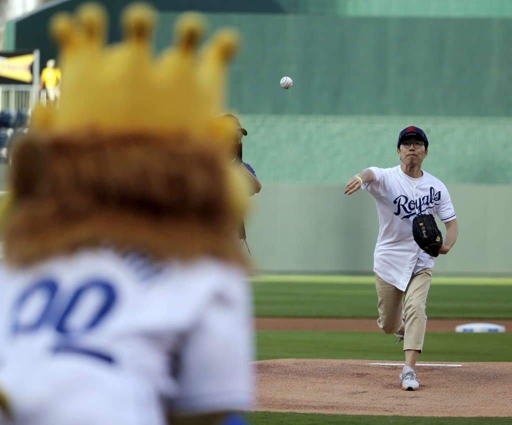 Longtime Kansas City Royals fan Sung Woo Lee, from South Korea, throws the ceremonial first pitch before a baseball game against the Oakland Athletics, Monday, Aug. 11, 2014, in Kansas City, Mo. (AP Photo/Charlie Riedel)