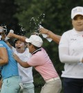 Lee Mi-rim of South Korea, left, is doused with water by other players and friends as Inbee Park, right, walks off the green after the second playoff hole of the final round during the Meijer LPGA Classic golf tournament at Blythefield Country Club, Sunday, Aug. 10, 2014, in Belmont, Mich. (AP Photo/Carlos Osorio)