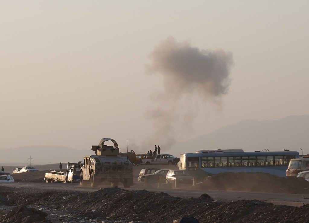 An armored vehicle belonging to Kurdish Peshmerga fighters rushes to a bombing site as smoke rises after airstrikes targeting Islamic State militants near the Khazer checkpoint outside of the city of Irbil in northern Iraq, Friday, Aug. 8, 2014. The Iraqi Air Force has been carrying out strikes against the militants, and for the first time on Friday, U.S. war planes have directly targeted the extremist Islamic State group, which controls large areas of Syria and Iraq.(AP Photo/ Khalid Mohammed)