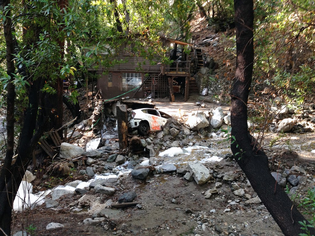 A car is lodged in the debris on Monday, Aug. 4, 2014, where a body was found Sunday that was swept into the rain-swollen water course in Mount Baldy, Calif. About 2,500 people were stranded early Monday after thunderstorms caused mountain mudslides in Southern California. (AP Photo/Brian Melley)