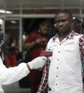 A Nigerian port health official uses a thermometer on a worker at the arrivals hall of Murtala Muhammed International Airport in Lagos, Nigeria, Wednesday, Aug. 6, 2014. A Nigerian nurse who treated a man with Ebola is now dead and five others are sick with one of the world's most virulent diseases, authorities said Wednesday, as the death toll rose to at least 932 people in four West African countries. (AP Photo/Sunday Alamba)