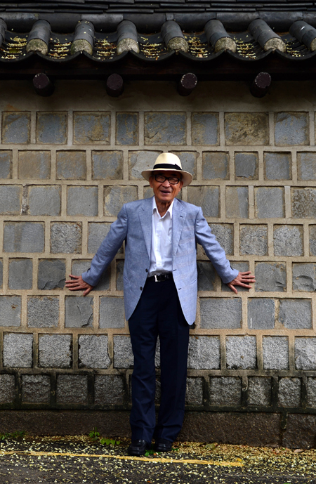 Poet Ko Un poses against the stone wall near Deoksu Palace in Seoul on a recent Sunday. (Shim Hyun-chul/The Korea Times)
