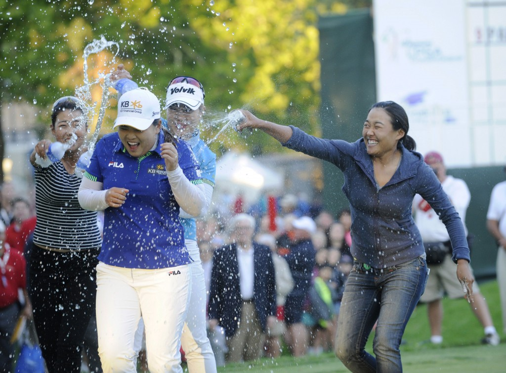 Jenny Shin, left, Meena Lee, center, and Illhee Lee, right, spray Champion Inbee Park after she won the Wegmans LPGA golf championship in Pittsford, N.Y., Sunday, Aug. 17, 2014. Park won in a sudden death playoff round. (AP Photo/Gary Wiepert)