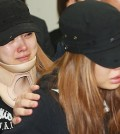 Zuny, left, and Ashley cannot hold back the tears at EunB's funeral. (Yonhap)