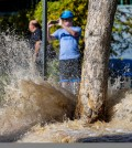People stopped to take pictures of flowing water along North Olive Drive, following a water main break on Sunset Boulevard, in West Hollywood, Friday, Sept. 26, 2014. (AP Photo/Los Angeles Times, Jay L. Clendenin)