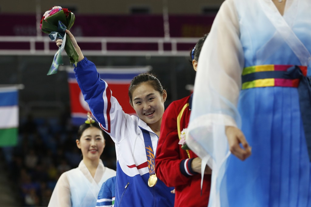 Gold medallist North Korea's Hong Un-jong raises her flower bouquet at the end of the medal ceremony for the gymnastics women's vault final at the 17th Asian Games in Incheon, South Korea, Wednesday, Sept. 24, 2014.  (AP Photo/Kin Cheung)