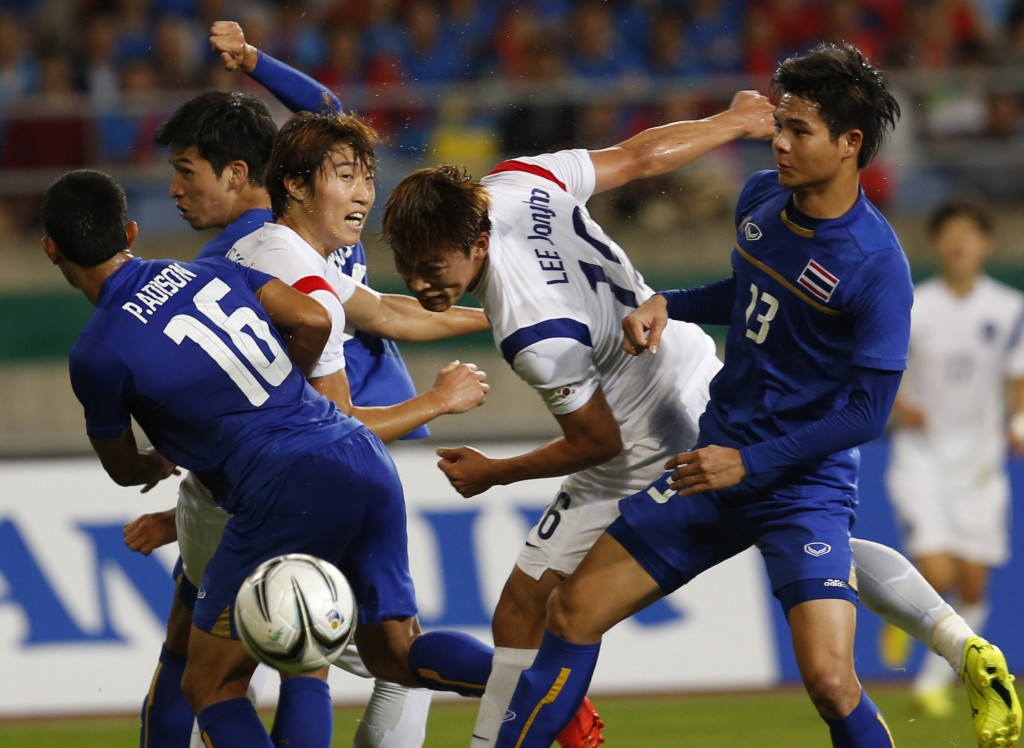 South Korea's Kim Seung-dae, center, fights for the ball with Thailand's Narubadin Weerawatnodom, right and Adison Promrak, left, during the men's football semifinal against Thailandat the 17th Asian Games in Incheon, South Korea, Tuesday, Sept. 30, 2014.  (AP Photo/Kin Cheung)