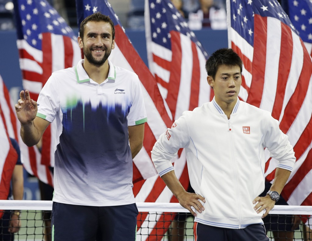 Marin Cilic, of Croatia, left, and Kei Nishikori, of Japan, stand for the trophy ceremony after Cilic defeated Nishikori in the championship match of the 2014 U.S. Open tennis tournament, Monday, Sept. 8, 2014, in New York. (AP Photo/Darron Cummings)