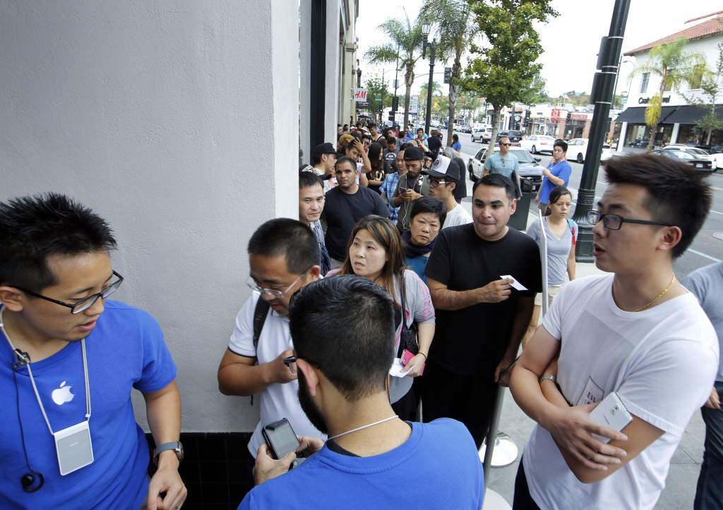 Apple customers await the opening of the Apple Store for the launch and sale of the new iPhone 6 on Friday, Sept 19, 2014 in Pasadena, Calif. The highly anticipated iPhone 6 and iPhone 6 Plus are being released in stores today.  (AP Photo/Damian Dovarganes)