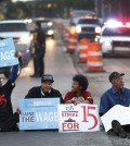 Protesters block traffic on Mack Avenue in Detroit as part of a national protest to push fast-food chains to pay their employees at least $15 an hour Thursday, Sept. 4, 2014. Hundreds of workers from McDonald's, Taco Bell, Wendy's and other fast-food chains are expected to walk off their jobs Thursday, according to labor organizers of the latest national protest to push the companies to pay their employees at least $15 an hour. (AP Photo/Paul Sancya)