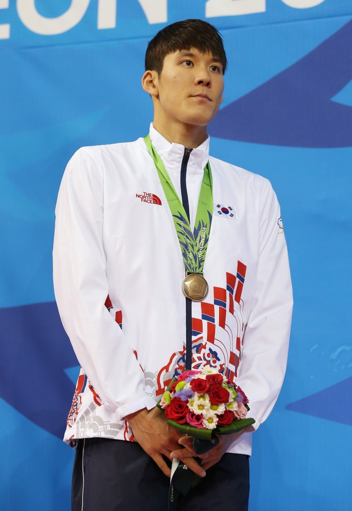 South Korea's Park Tae-hwan  stands on the podium with his bronze medal following the men's 400-meter freestyle relay final at the 17th Asian Games in Incheon, South Korea,  Tuesday, Sept. 23, 2014.(AP Photo/Rob Griffith)