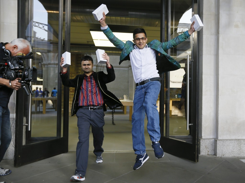 The first people in the queue, Sam Sheikh, left, and Jameel Ahmed, right, celebrate for the media after buying the new iPhone6, outside the Apple shop in London, Friday, Sept. 19, 2014. The new Apple iPhone6 went on sale at the shop on Friday. (AP Photo/Kirsty Wigglesworth)
