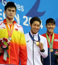 From left, silver medalist China's Sun Yang, gold Japan's Kosuke Hagino and bronze South Korea's Park Tae-hwan  pose for  photo on the podium after the men's 200-meter freestyle swimming final at the 17th Asian Games in Incheon, South Korea,  Sunday, Sept. 21, 2014.(AP Photo/Rob Griffith)