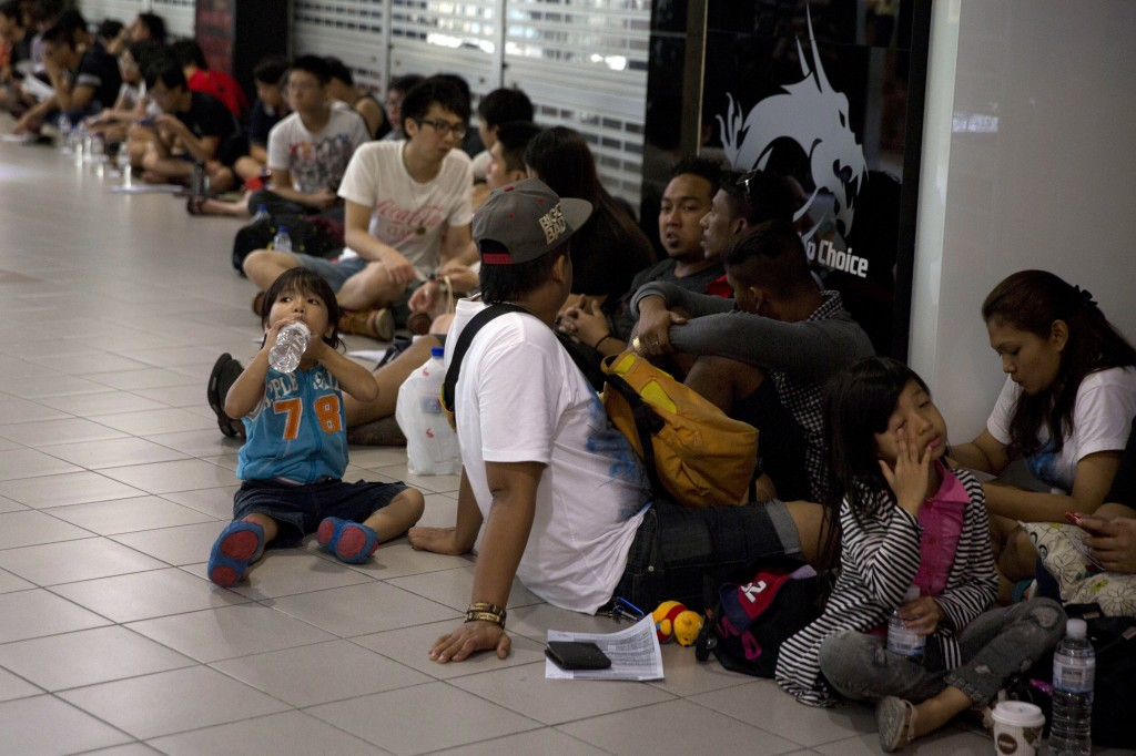 Shoppers wait inline to buy Apple's latest iPhones outside a reseller in Singapore, Friday, Sept. 19, 2014. Apple's newest mobile devices, the iPhone 6 and iPhone 6 Plus go on sale Friday. (AP Photo/Ng Han Guan)