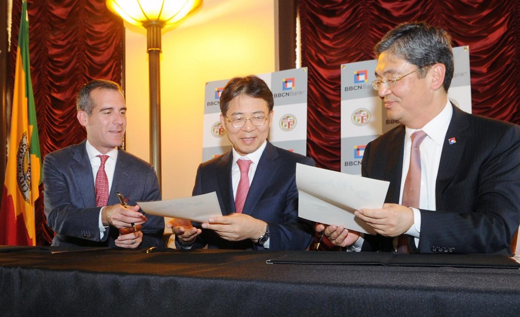 Los Angeles Mayor Eric Garcetti, left, signs an MOU at a trade symposium at city hall Wednesday, joined by Korean Consul General Kim Hyun-myung, center, and BBCN Bank President and CEO Kevin Kim.