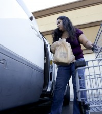 Irma Salazar,  of Santa Ana, Calif., loads plastic grocery bags into her car, Tuesday, Sept. 30, 2014 in Santa Ana, Calif. Gov. Jerry Brown has signed legislation on Tuesday imposing the nation's first statewide ban on single-use plastic bags.(AP Photo/Chris Carlson)