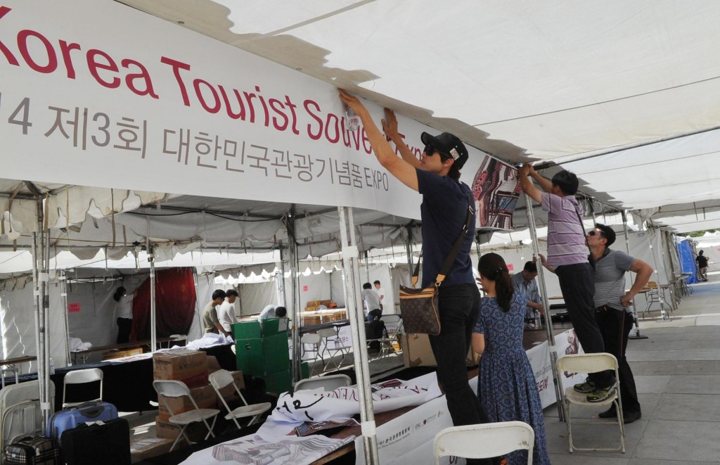 People from Korea Tourist Souvenir Expo are putting up a banner on their booth.  (The Korea Times / Park Sang-hyuk)