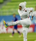 FILE- In this Sept. 18, 2014 file photo Jordan's Anfal Nayef Hammad Alsufy kicks a ball down filed during her team's football match against Japan at the 17th Asian Games in Incheon, South Korea. Qatar's delegation chief says the women's basketball team has withdrawn from the Asian Games after organizers refused to let players wear hijabs in competition. (AP Photo/Kin Cheung,File)