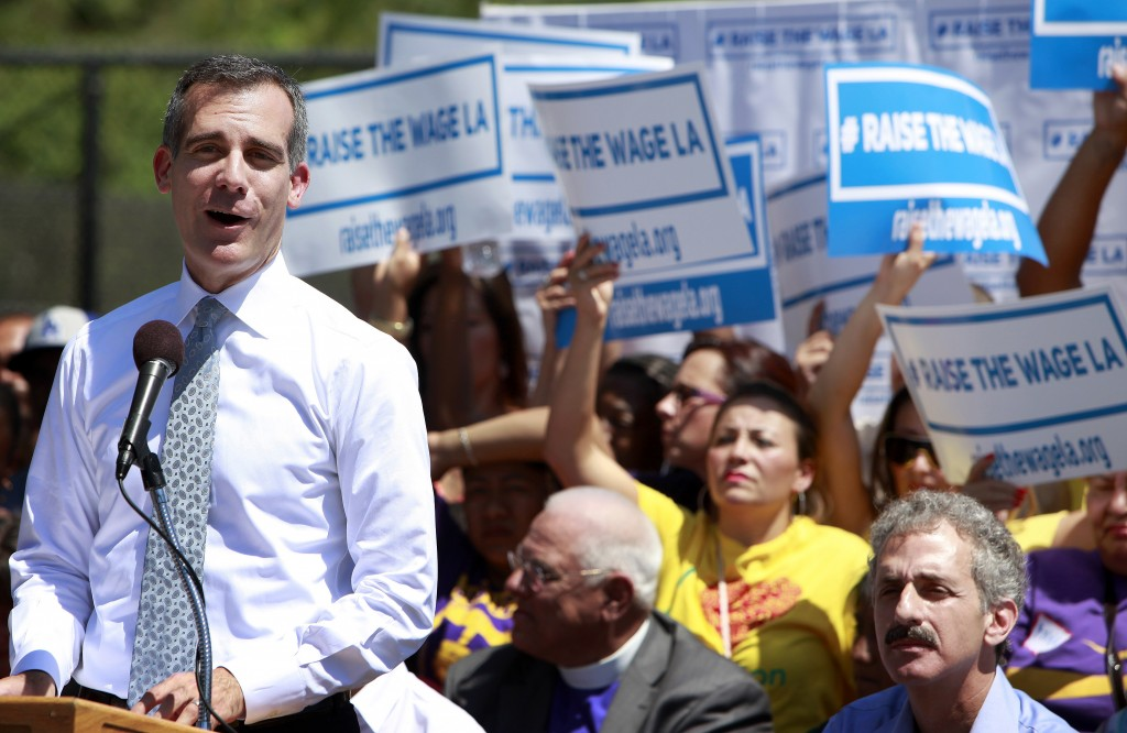 Los Angeles Mayor Eric Garcetti makes an announcement at the Martin Luther King, Jr. Park in South Los Angeles with a coalition of business, labor, community, and faith leaders from across the city on Monday, Sept. 1, 2014. Garcetti announced his proposal to raise the minimum wage in Los Angeles from the current $9 per hour to $13.25 in 2017. (AP Photo/Richard Vogel)
