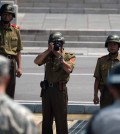 A North Korean soldier takes picture of an American soldier and a Korean military police officer at Panmujeom. (Newsis)