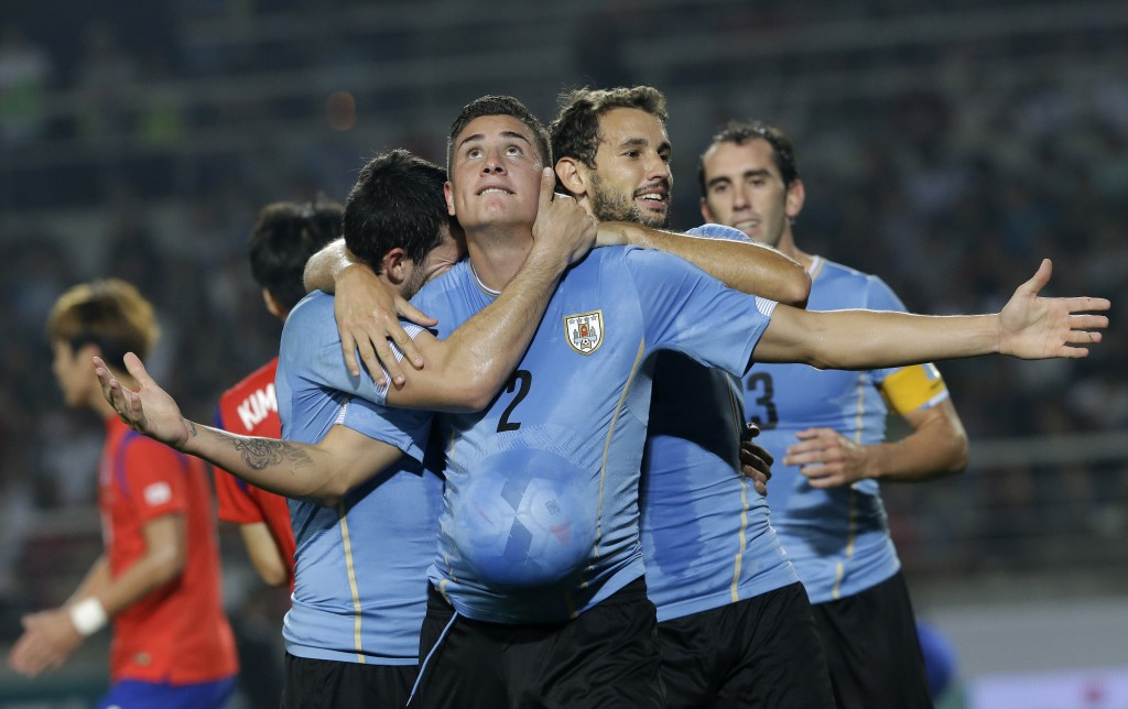 Uruguay's Jose Gimenez, center, celebrates with his teammates after scoring a goal against South Korea during their friendly soccer match at Goyang Stadium in Goyang, South Korea, Monday, Sept. 8, 2014. Uruguay defeated South Korea 1-0. (AP Photo/Ahn Young-joon)