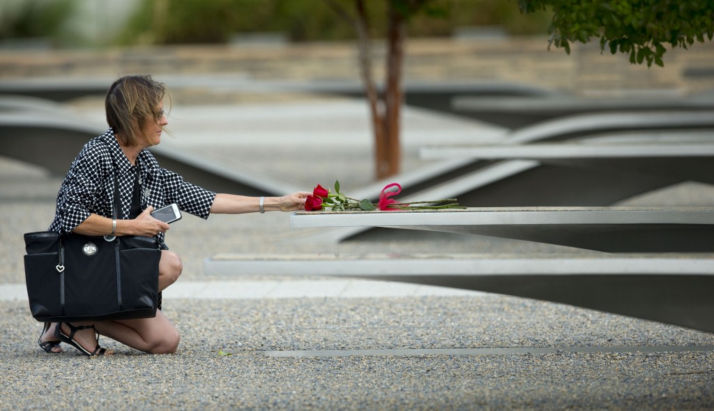 A woman reaches out to touch rose on one of the benches of the Pentagon Memorial at the at the Pentagon, Thursday, Sept. 11, 2014. (AP Photo/Pablo Martinez Monsivais)