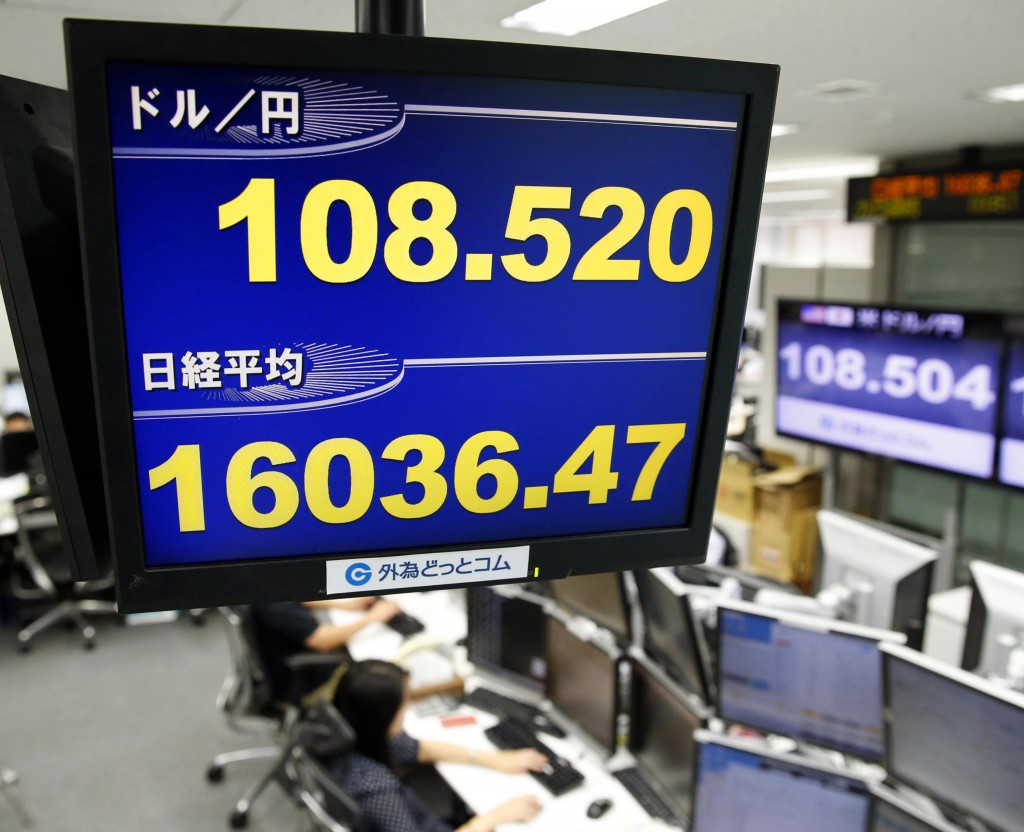 Japan Financial Markets Money traders of a foreign exchange dealing company work under an electric screen indicating the U.S. dollar against the Japanese yen in Tokyo Thursday, Sept. 18, 2014. The U.S. dollar hit its highest level against yen in six years. (AP Photo/Kyodo News)