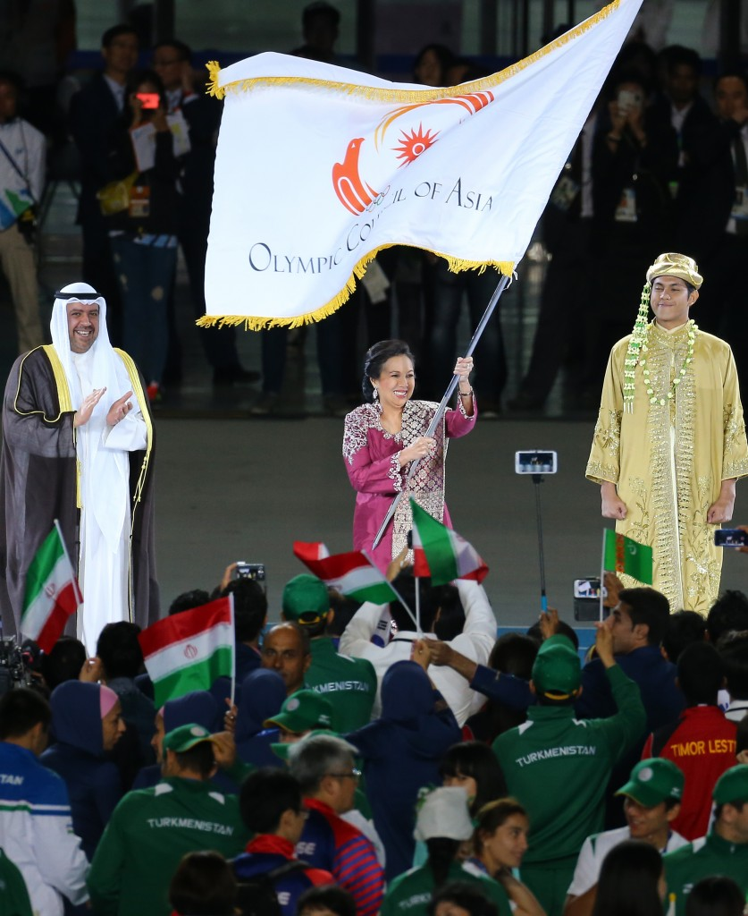 Rita Subowo, middle, President of National Olympics Committee of Indonesia, holds the Olympic Council of Asia flag during the closing ceremony for the 17th Asian Games in Incheon, South Korea, Saturday, Oct. 4, 2014. (Yonhap)