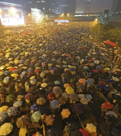 Pro-democracy protesters hold umbrellas under heavy rain in a main street near the government headquarters in Hong Kong, late Tuesday, Sept. 30, 2014. Pro-democracy protesters demanded that Hong Kong's top leader meet with them on Tuesday and threatened wider actions if he did not, after he said China would not budge in its decision to limit voting reforms in the Asian financial hub. (AP Photo)