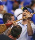 A Kansas City Royals fan celebrates with a broom during the sixth inning of Game 3 of baseball's AL Division Series against the Los Angeles Angels in Kansas City, Mo., Sunday, Oct. 5, 2014. (AP Photo/Orlin Wagner)